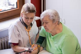 An assisted living nurse monitors the blodd pressure of a resident